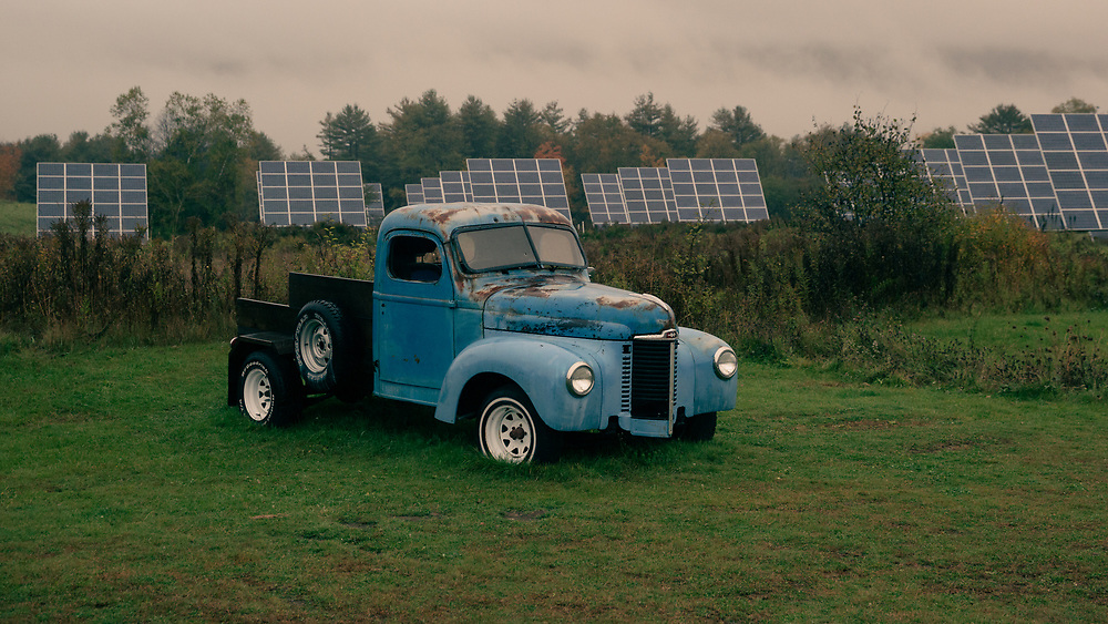 An old truck sitting in front of a field of solar panels on a rainy autumn morning in Vermont.