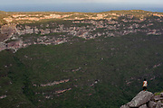Valley de Capao, famaca waterfall valley with young man standing on a rock looking at the view at dusk. Chapada Diamantina national park in Bahia, Brazil is a very large park conprising miles of trails, several settlements and spectacular scenery
