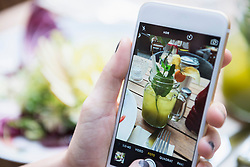 Hands of woman taking picture of mocktail