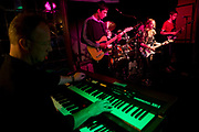 An adult keyboard player accompanies a young teenage band who perform in a south London pub during a music showcase. The man is a dad whose hands play the keys on the electric piano on a rock and roll number that the young people have learned over the last few weeks. A young girl is lead singer and older boys play a Telecaster lead guitar and bass. Organised by a south London guitar teacher who brings in sound equipment, the kids play their rehearsed songs for a private audience of parents and friends.