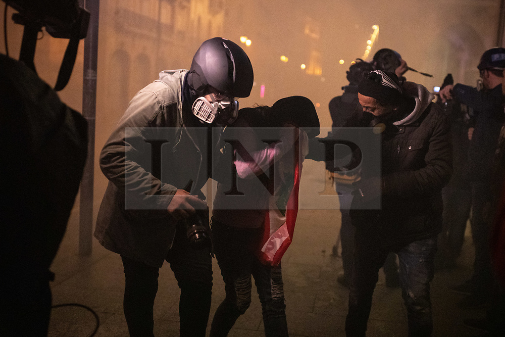 """© Licensed to London News Pictures. 22/01/2020. Beirut, Lebanon. Media help an injured demonstrator during riots outside government buildings on the streets of Beirut following the announcement late last night that a government has been formed. Police respond with tear gas and water cannon against the anti-government demonstrators. Violence has been escalating in the capital following a """"week of wrath"""", where demonstrators were campaigning against government corruption and economic crisis. Photo credit : Tom Nicholson/LNP"""