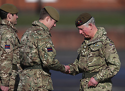 The Prince of Wales (right) presents campaign medals to soldiers from the 1st Battalion Welsh Guards at Elizabeth Barracks in Woking, following their return from Afghanistan.