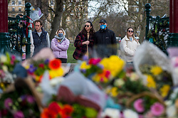 © Licensed to London News Pictures. 13/03/2021. LONDON, UK.  London, UK.  13 March 2021.  People view floral tributes at the bandstand on Clapham Common to remember Sarah Everard.  Wayne Couzens, 48, a serving Met Police officer, has been charged with her kidnap and murder after she walked home in south London.  The 33-year-old's body was found in woodland in Kent more than a week after she was last spotted on 3 March.  Photo credit: Stephen Chung/LNP