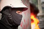 18 MAY 2010 - BANGKOK, THAILAND:  An anti government protester takes cover begind a burning tire barricade at Din Daeng Intersection in Bangkok Tuesday. The intersection has been under periodic sniper fire from unidentified snipers near Thai military lines. Violent unrest continued in Bangkok again Tuesday nearly a week after Thai troops started firing on protesters and Bangkok residents took to the streets in violent protest against the government. Tuesday was not as violent as previous days however. Although protesters continued to set up roadblocks and flaming tire barricades across parts of the city, there was not as much gunfire from the government lines. The most active protesters were at the Din Daeng Intersection about a mile from the Red Shirts' Ratchaprasong camp.  PHOTO BY JACK KURTZ