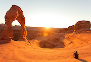Hiker watching sunset at Delicate Arch, Wind sculpted archway, Arches National Park, Utah, United States of America