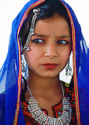 A young girl in traditional costume with silver filigree necklace and earrings and a brightly coloured veil, Pakistan