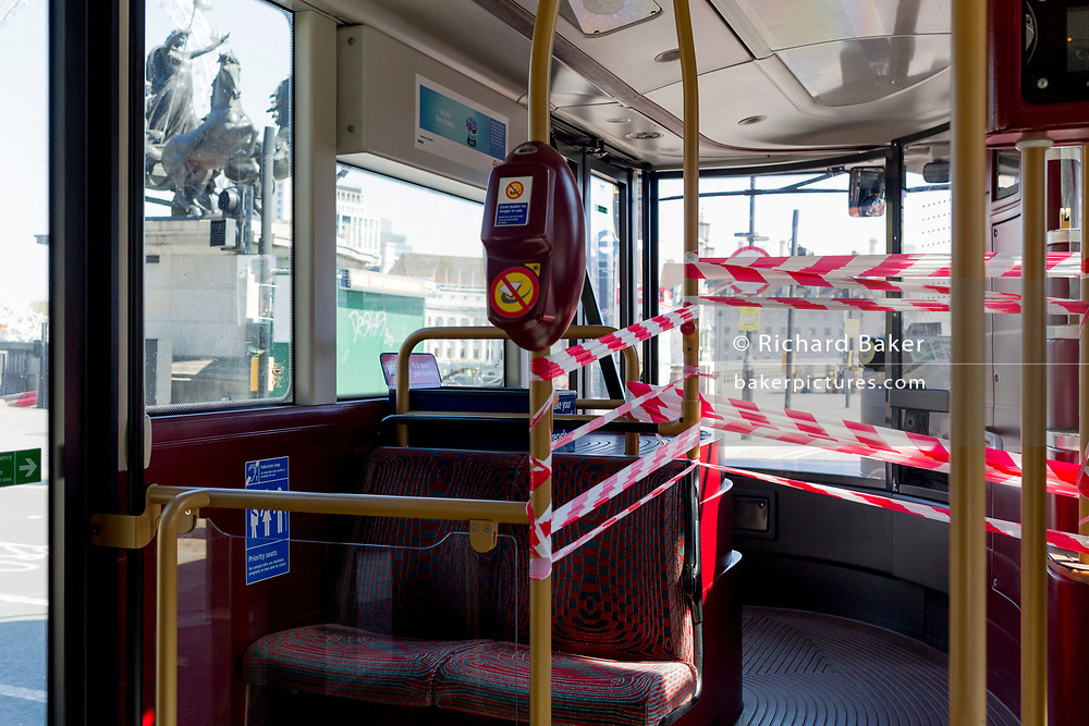 At the beginning of the fourth week of the UK government's lockdown during the Coronavirus pandemic, and with 120,067 UK reported cases with 16,060 deaths, a number 12 bus passes Boudicca's statue on Westminster Bridge with the front door taped off, a measure that reduces the proximity between bus passengers and drivers after 20 drivers have died from Covid-19 across the country, on 20th April 2020, in London, England. Passengers embark through middle doors and payment keypads on London buses have been disabled so no fares are currently being taken, on 20th April 2020, in London, England.