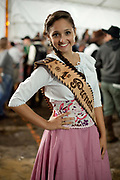 Young female gaucha cowgirl girl, portrait looking at camera and smiling, wearing competition pageant sash. Gaucho cowboy Rodeo, Flores de Cunha, Rio Grande do Sul.