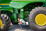 """06 AUGUST 2020 - FAIRFIELD, IOWA: A man checks out the engine of a combine for sale during the auction on the Adam Farm near Fairfield. Gary Adam, 72 years old, has been farming in the Fairfield area since 1971. He decided to retire this year because he wants to travel and because it's so difficult to make money in farming this year. He said he wants to """"shed the risk and responsibility. If things were super good, like they were 2006-2012, I might stay in it, but they're not."""" An increasing number of farmers in the Midwest are retiring this year as it becomes harder to make money on crops. In addition to low prices, Iowa farmers are being hit with a drought this year, with well below average rain over most of the state. Because of the COVID-19 pandemic, the auction on Adam's farm was one of the first live in person auctions since winter. Most auctions are now done on line.    PHOTO BY JACK KURTZ"""
