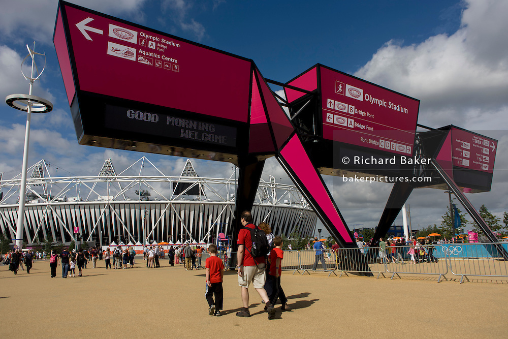 Arriving spectators pass underneath the large gateway to the Olympic Park during the London 2012 Olympics. This land was transformed to become a 2.5 Sq Km sporting complex, once industrial businesses and now the venue of eight venues including the main arena, Aquatics Centre and Velodrome plus the athletes' Olympic Village. After the Olympics, the park is to be known as Queen Elizabeth Olympic Park.