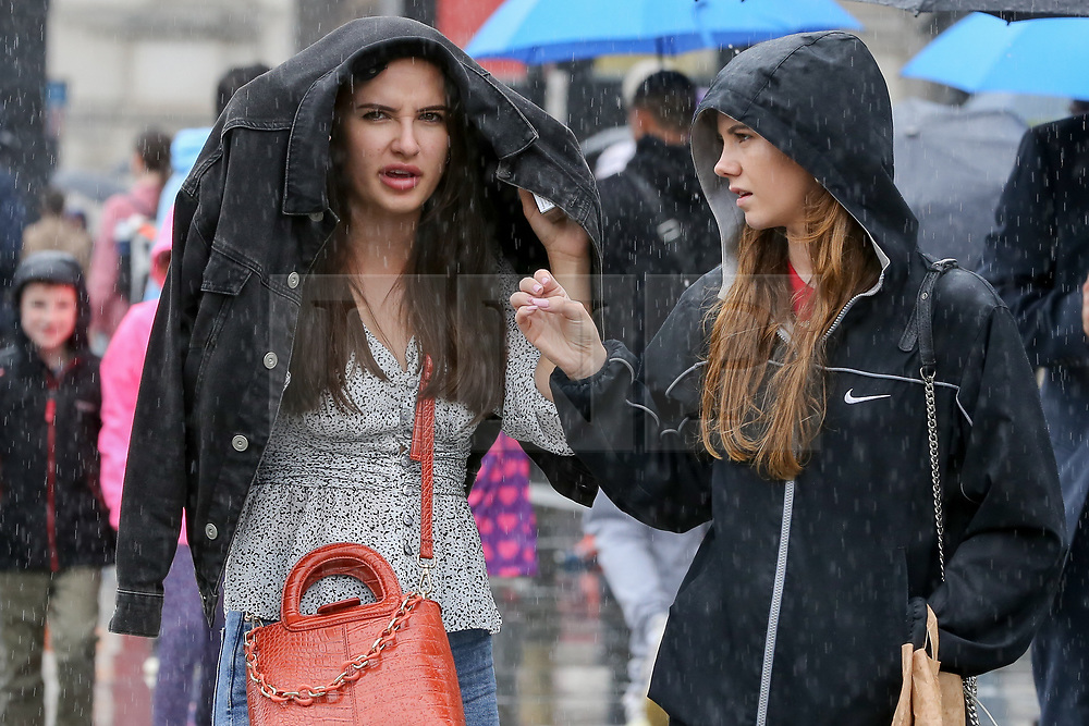 © Licensed to London News Pictures. 16/08/2019. London, UK. A woman shelters from the rain under her jacket during a heavy downpour in Trafalgar Square. The Met Office has issued a severe weather alert for most of today, as almost a month's worth of rain is expected in many parts of the UK. Photo credit: Dinendra Haria/LNP