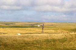 Old west style windmill dots the landscape standing as a landmark against the prairie horizon in Northwest Nebraska