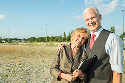 Smiling mature couple with clipboard at development area
