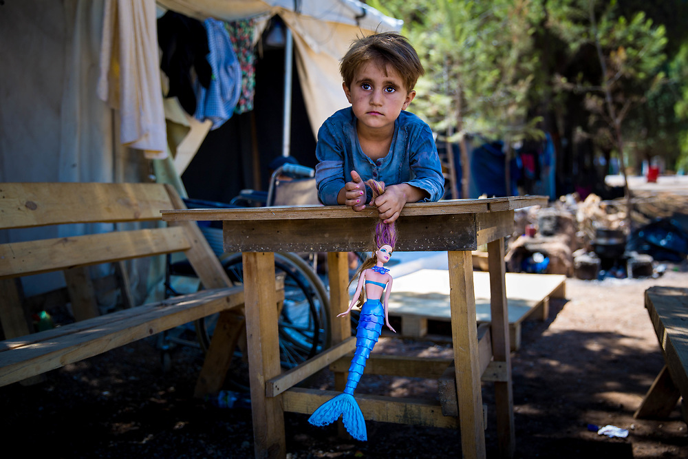 """Najah, 4, a Kurdish Syrian refugee from Aleppo, plays on a table her Grandpa Jameel made, which sits outside of her family's tent in Ritsona Refugee Camp, an hour north of Athens, Greece. July 2016.<br /> <br /> extended family have been stranded in Greece since they arrived in March 2016, after the Balkan borders were closed to all refugees. Referring to their extended family, Grandpa Jameel said, """"We are happy to go anywhere, as long as we can stay together."""""""