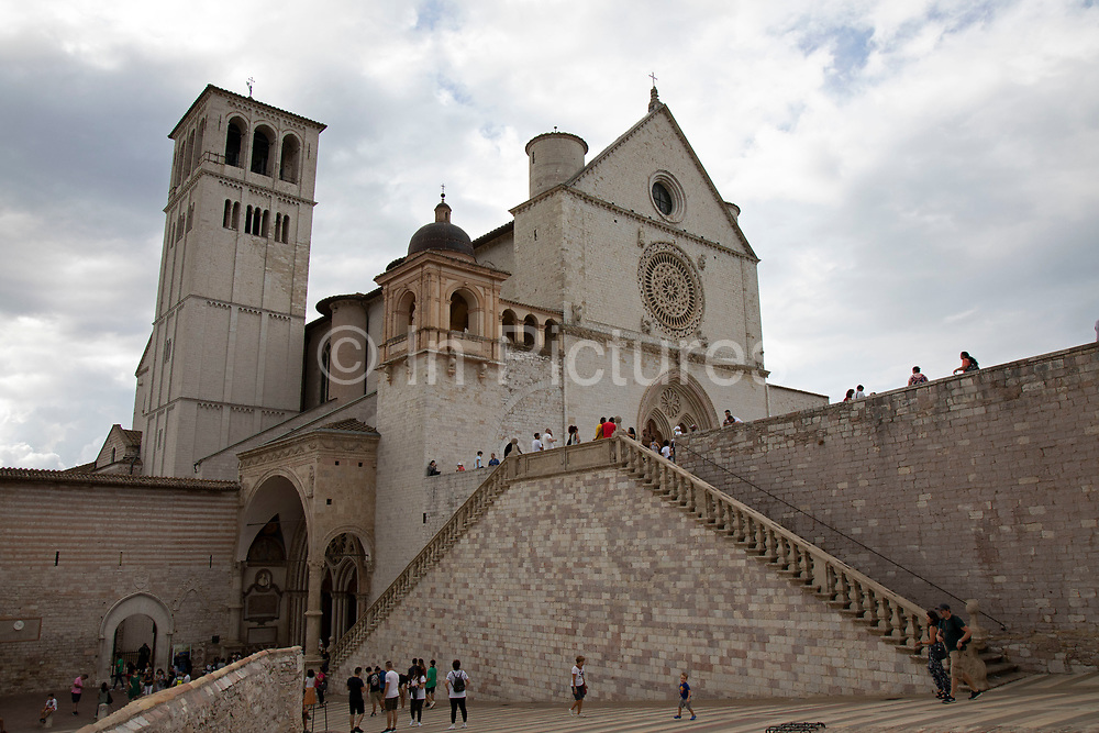 Exterior with tourists at the Basilica of San Francesco dAssisi in Assisi, Umbria, Italy. The Papal Basilica of Saint Francis of Assisi is the mother church of the Roman Catholic Order of Friars Minor Conventual in Assisi, a town of Umbria region in central Italy, where Saint Francis was born and died. The basilica is one of the most important places of Christian pilgrimage in Italy. Assisi is a town in the Province of Perugia in the Umbria region, on the western flank of Monte Subasio. It is generally regarded as the birthplace of the Latin poet Propertius, and is the birthplace of St. Francis, who founded the Franciscan religious order in the town in 1208, and St. Clare, Chiara dOffreducci, the founder of the Poor Sisters, which later became the Order of Poor Clares after her death. Assisi is now a major tourist destination for those sightseeing or for more religious reasons.