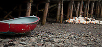 Fisherman's dingy and lobster bouys tied to a pier at low tide in Bass Harbor Maine.