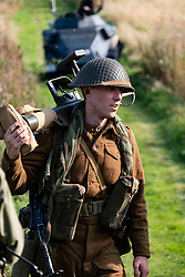 World War 2 Reenactors portray a British Infantry PIAT antitank team from The Duke of Wellingtons Regiment, Polar Division during the second world war walk away from the battlefield after destroying a German armoured car. <br /> The PIAT (Projector, Infantry, Anti Tank) was a British man-portable anti-tank weapon developed during the Second World War based on the Spigot Mortar system and had an effective range of 115 yards or 105 meter