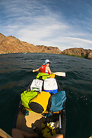 Canoer takes a break to pose for a photo while a a trip through The Black Canyon, Nevada.