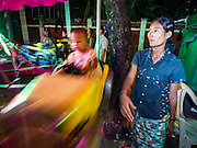 29 OCTOBER 2015 - YANGON, MYANMAR: A worker gets a Merry Go Round spinning during a street carnival in central Yangon. Electricity is scarce in Myanmar, especially in rural areas, and most traveling carnivals use human powered rides. Workers climb to the top of the Ferris Wheel and then pull it around getting it spinning. They do the same with Merry Go Rounds, but instead of climbing to the top they pull it around. The carnival coincided with the Thadingyut Festival, the Lighting Festival of Myanmar, which is held on the full moon day of the Burmese Lunar month of Thadingyut, October or November on the Gregorian calendar. The carnival featured food, rides and games.      PHOTO BY JACK KURTZ