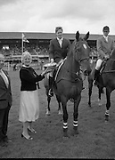 """Shell Puissance Competition R.D.S..1985..07.08.1985..08.07.1985..7th August 1985..The Shell sponsored Puissance was held in the R.D.S.Dublin during Dublin Horse Show week..Image shows Mrs Olga Beveridge,wife of the Managing Director of irish Shell Ltd,.presenting the winners trophy to Mr Trevor Coyle. Mr Coyle won aboard his mount """"Bank Strike"""".Mr Beveridge is pictured alongside his wife."""