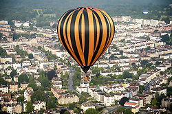 A hot air balloon passes over the city of Bristol during a mass balloon launch from Clifton Downs to mark less than a week to go until the start of the Bristol International Balloon Fiesta.