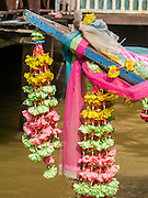 """05 OCTOBER 2012 - BANGKOK, THAILAND:   Flower garlands on the bow of a """"long tail"""" boat on the Chao Phraya River in Bangkok, Thailand. Long tail boats are narrow boats used as taxis on the waterways of Thailand. Bangkok used to be criss crossed by canals and boats were the way people got around. Now most of the canals have been filled in and paved over.     PHOTO BY JACK KURTZ"""