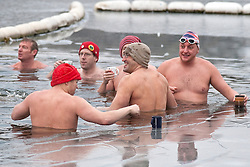 © under license to London News Pictures. 25/12/10. Members of the Serpentine Swimming Club brave ice and freezing temperatures to take part in their annual Christmas day swim in Hyde Park, London. Swimmers rest their cups on the ice covering the Serpentine as they prepare to start swimming. Credit should read Matt Cetti-Roberts/London News Pictures