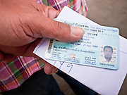 03 JULY 2011 - SAMUT PRAKAN, THAILAND:   A man holds his national ID card before voting in Samut Prakan, Thailand, Sunday, July 3. More than 47,000,000 Thais were registered to vote in Sunday's election, which had turned into a referendum on the current government, led, by the Thai Democrats and the oppositionPheu Thai party. Pheu Thai is the latest political incarnation of ousted Thai Prime Minister Thaksin Shinawatra. PT is led by his youngest sister, Yingluck Shinawatra, who is the party's candidate for Prime Minister. Exit polling by three Thai polling firms showed Pheu Thai winning a landslide election.     PHOTO BY JACK KURTZ