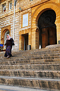 Beirut, Lebanon - September 23, 2010: A Muslim woman walks into the American University of Beirut (AUB), founded in 1866. The educational philosophy, standards, and practices of AUB are based on the American liberal arts model of higher education; it has around 700 instructional faculty and a student body of around 8,000 students. Engraved on the wall to the left of the entrance is this passage drawn from the New Testament: THAT THEY MAY HAVE LIFE AND HAVE IT MORE ABUNDANTLY