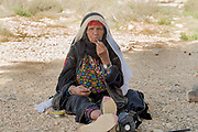 Israel, Negev Desert, mature Bedouin woman in traditional dress smokes a pipe
