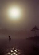 Canoeing through morning mist on Canoe Lake, Algonquin Provincial Park, Ontario, Canada.