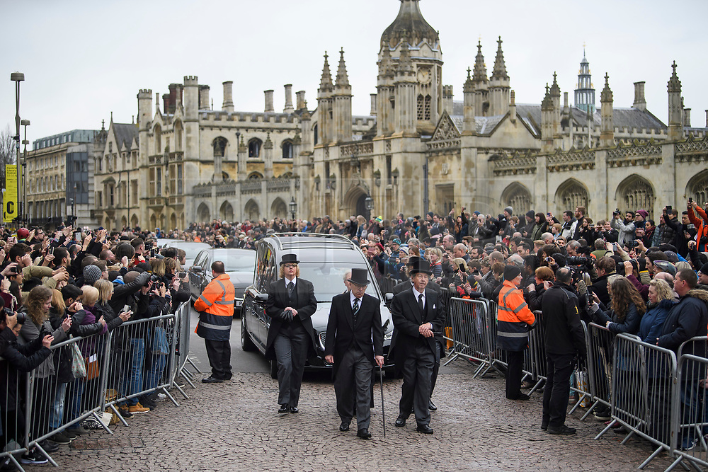 © Licensed to London News Pictures. 31/03/2018. Cambridge, UK. Members of the public watch as the funeral procession arrives. The funeral of Stephen Hawking at Church of St Mary the Great in Cambridge, Cambridgeshire. Professor Hawking, who was famous for ground-breaking work on singularities and black hole mechanics, suffered from motor neurone disease from the age of 21. He died at his Cambridge home in the morning of 14 March 2018, at the age of 76. Photo credit: Ben Cawthra/LNP