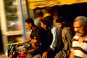 Egypt, 2000 - Four riders on motorcycle weave though Cairo traffic. Camera has panned to catch moving motorcycle in focus while background is blurred.