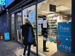 © Licensed to London News Pictures. 27/03/2020. London, UK.  Customers queue outside a west London supermarket. A new policy of 'one in one out'  is strictly applied by a security guard on the door of the Co-op supermarket on Uxbridge Road, Shepherd's Bush. A maximum of 3 customers at a time are allowed inside the store as retail businesses look to enforcing social distancing guidelines. Photo credit: Guilhem Baker/LNP