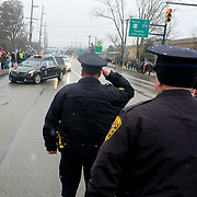 Police officers salute as the hearse carrying slain Toledo Police Department Officer Brandon Stalker passes by during the funeral procession at Toledo Memorial Park in Sylvania, Ohio, on Tuesday, Jan. 26, 2021. THE BLADE/KURT STEISS