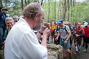 Runners stream by Laz after he lights his cigarette at the yellow gate in Frozen Head State Park to start the Barkley Marathons.