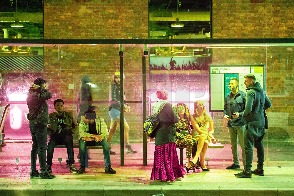 © Licensed to London News Pictures . 28/10/2018. Manchester, UK. Revellers sit in a bus shelter in Stevenson Square in the Northern Quarter of Manchester City Centre . Revellers on a night out , many in fancy dress , on the weekend before Halloween . Photo credit: Joel Goodman/LNP