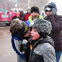 Aiden Stephens, 9, receives a kiss from his mom Savanna Stephens after finishing the Quad Kids race, Saturday, Feb. 16, in Grants during the Mt. Taylor Winter Quadrathlon.