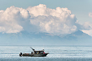 A fishing charter boat waits for a tractor tug that will carry it back to land on the beach at Anchor Point, Alaska. The unique boat launch uses logging skidders to tow fishing boats from the Cook Inlet up the steep beach to the parking area and is the result of extreme tide that would make launching a boat impossible otherwise.