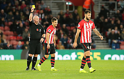 Match referee Simon Hooper shows Southampton's Cedric Soares the yellow card during the Premier League match at St Mary's Stadium, Southampton.