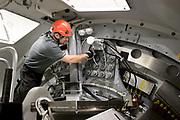 Technician working inside a wind turbine nacelle.