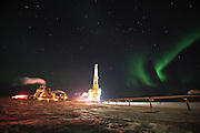 A drilling rig moves to another drill site as the northern lights dance over the pipeline at Alpine Oilfield on Alaska's north slope.