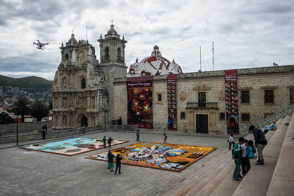 A drone hovers above art work made during Day of the Dead (Día de los Muertos) festivities in Oaxaca, Mexico. The church in the background is the Basilica of Our Lady of Solitude built between 1682 and 1690.