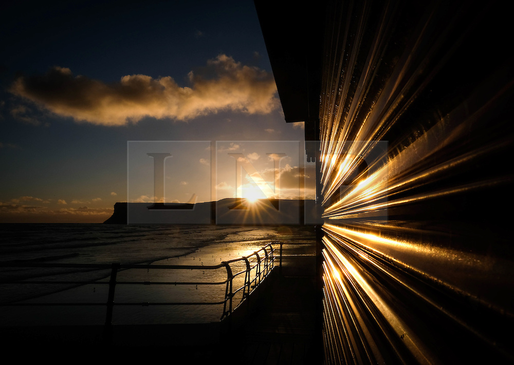 © Licensed to London News Pictures. <br /> 02/10/2016. <br /> Saltburn-by-the-Sea, UK.  <br /> <br /> The sun rises over cliffs at Saltburn-by-the-Sea and reflects off building shutters on the pier.<br /> <br /> Photo credit: Ian Forsyth/LNP