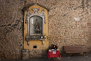 Above a street trader is the shrine to Sao Jorge Saint George, near the entrance of his namesake, Castelo de Sao Jorge, on 13th July 2016, in Lisbon, Portugal.
