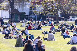 Licensed to London News Pictures. 18/04/2021. London, UK. Members of the public soak up the sunshine in Richmond Green, South West London on the first weekend of the easing of Covid-19 restrictions. Shops, pubs, bars and restaurants are now serving customers for the first time in over 4 months as a mini heatwave is set to hit the UK this week with temperatures predicted to reach up to 18c in London and the South East. Photo credit: Alex Lentati/LNP