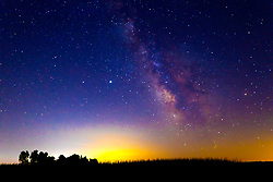 The Milky Way provides a colorful backdrop for a field of corn at night.