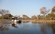 A 4x4 vehicle from Abu Camp, a luxury safari camp, drives through the waters of the Okavango Delta, Botswana