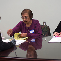 020315      Cayla Nimmo<br /> <br /> Dorella Zenz, left, and June Baca, right, help sign a voter in for the school board election held in Grants Tuesday.