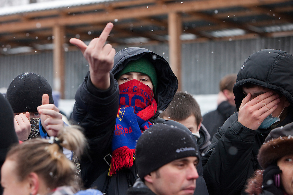 Moscow, Russia, 15/01/2011..Nationalists and football fans gesture at the media during a rally at the bus stop where Spartak soccer fan Yegor Sviridov was killed in a street fight with a group of men from the southern Caucasus, leading to a nationalist backlash that has spilled into racist violence on the streets of Moscow and other Russian cities. The rally on the 40th day after Sviridov's death was attended by a mixture of local people, football fans and Russian nationalists.